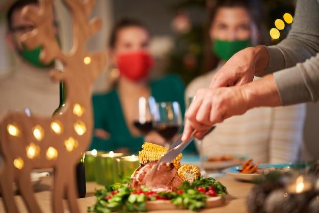 Kerstham die op tafel wordt geserveerd, mensen met maskers op de achtergrond