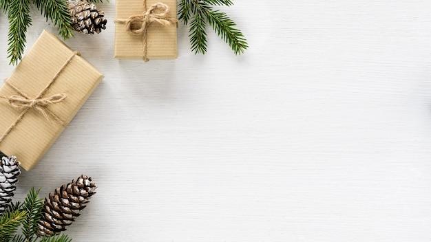 Kersthoekcompositie gemaakt van dennentakken, kegels geschenkdozen verpakt in kraftpapier op witte houten achtergrond. platliggend, bovenaanzicht, kopieerruimte