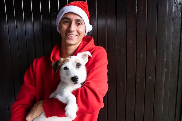 Kersthond en jonge man met kerstmuts gelukkige momenten lachend gezicht met kerstmis