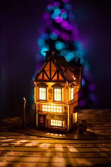 Kersthuis gemaakt met uw eigen handen van karton en papier, een huis met een gloeilamp en een kerstboom