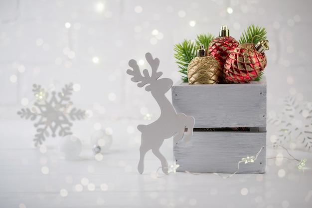 Kersthuisdecoratie met groene dennentakken, herten en lichten