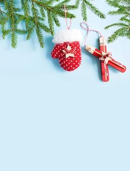 Kerstindeling wintersport met een vuren tak. speelgoed ski's, wanten, blauwe achtergrond.