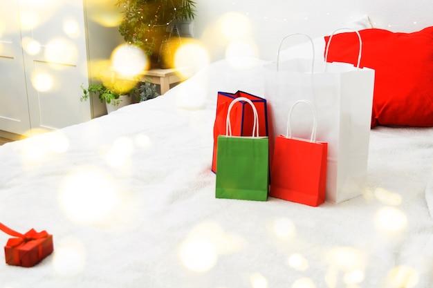 Kerstinkoopconcept met papieren zakken en geschenkdoos op bed thuis