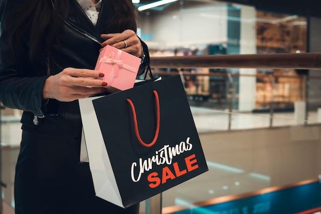 Kerstinkopen doen. gelukkige vrouw met boodschappentassen in shopping mall.sales. kerstcadeaus. winkelcentrum. vrouwenhanden stoppen een kerstcadeau in het pakket
