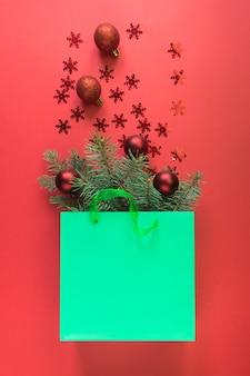 Kerstinkopen groene papieren zak met rode kerstballen en glanzende sneeuwvlokken op rode ruimte