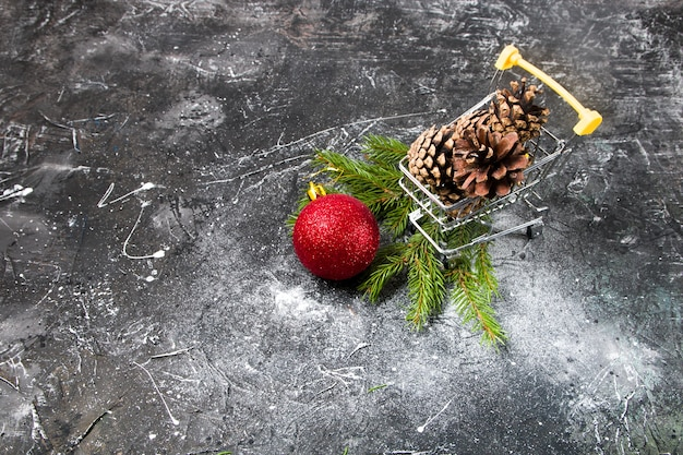 Kerstinkopen, online winkelen, winkelwagentje met dennenappels en rode kerstbal, vuren tak, zwarte achtergrond, kopieer ruimte