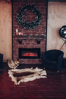 Kerstinterieur versierd met kerstkrans gemaakt van dennentakken. twee fauteuils en een echt dierenbont op de vloer voor een elektrische haard.