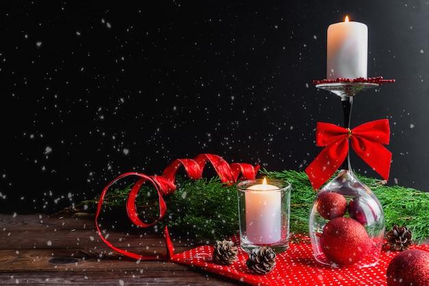 Kerstkaars op een omgekeerd glas, vuren pijnboomtakken en kerstversiering