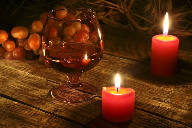 Kerstkaarsen, druiven en glas met cognac of whisky