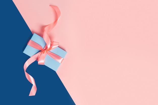 Kerstkaart. blauwe doos met een roze strik op tweekleurige tafel.