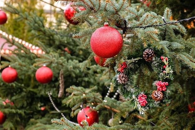 Kerstkaart. close-up van rode nieuwjaar ballen en garland op takken van natuurlijke kerstboom buiten op zonnige winterdag. geen mensen, geen sneeuw.