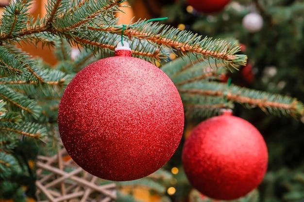 Kerstkaart. close-up van twee rode ballen van het nieuwjaar op een tak van natuurlijke kerstboom