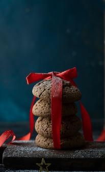 Kerstkaart, donkere achtergrond, speelgoed en zelfgemaakte koekjes in een blikje. hoge kwaliteit foto