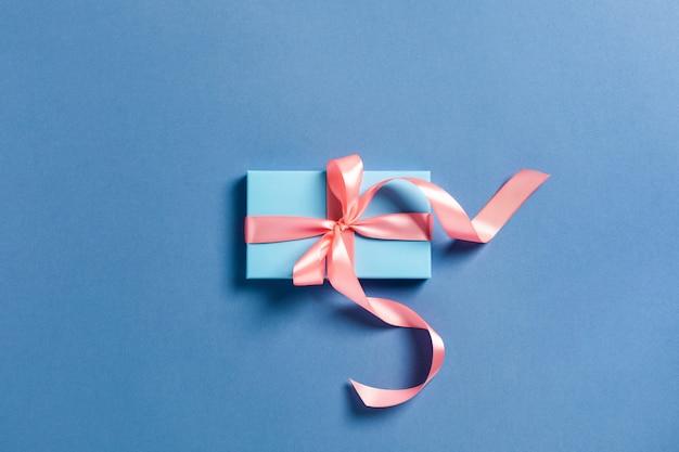 Kerstkaart. een blauwe doos met een roze strik.