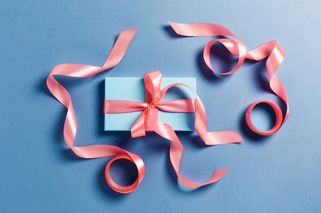 Kerstkaart. een blauwe doos met een roze strikjes.