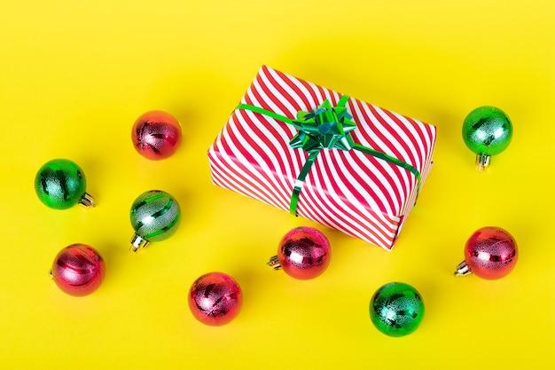 Kerstkaart met geschenkdoos en glanzende ballen op een gele muur.