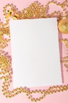 Kerstkaart met gouden feestelijke decoratie op een roze pastel achtergrond.