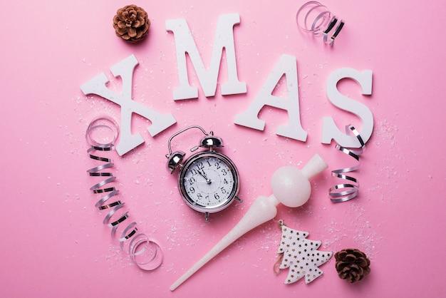 Kerstkaart met letters en klok op de roze achtergrond. kerst concept, top-down weergave