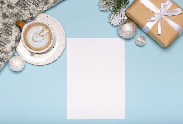 Kerstkaart met papier geschenkdoos en koffie op blauwe achtergrond