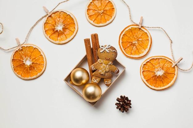 Kerstkaart met peperkoekmannetje, kaneel, gedroogde stukjes sinaasappel en kerstmisspeelgoed