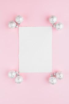 Kerstkaart met witte ballen decoratie op een roze pastel achtergrond.