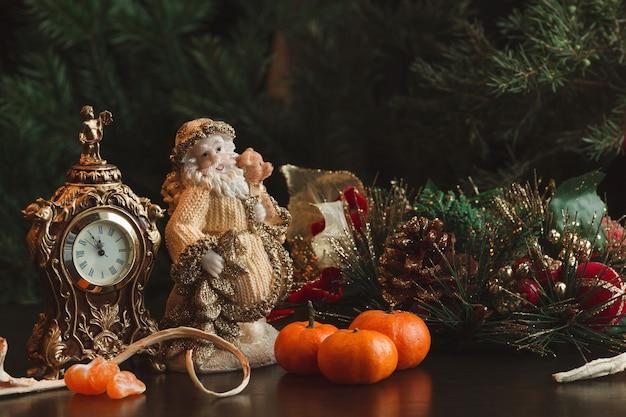 Kerstkaart. nieuwjaar. samenstelling klok, mandarijnen, kerstman op de achtergrond van dennentakken