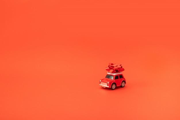 Kerstkaart of decor samenstelling met rode kleine speelgoedauto met een strik op een rode achtergrond met copyspace