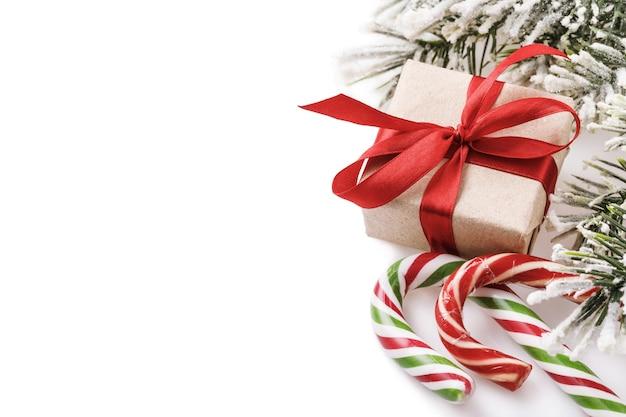 Kerstkaart op witte achtergrond met cadeausnoepjes fir branch en kopieer ruimte