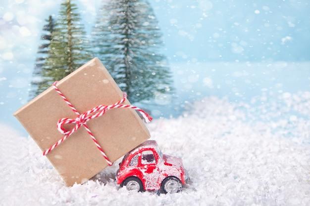 Kerstkaart voor kerstmis en nieuwjaar. vakantie samenstelling met pijnbomen, rode speelgoedauto en geschenkdoos.