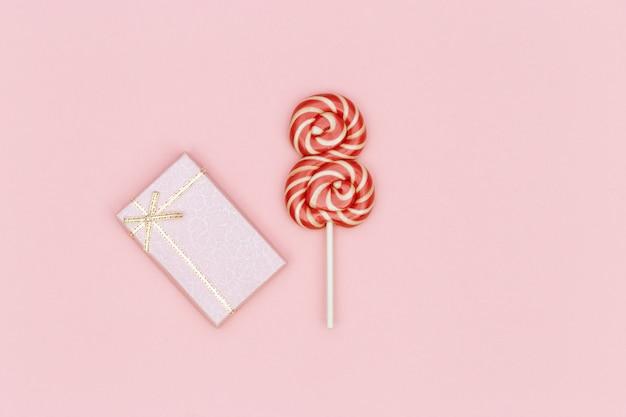 Kerstkaart voor vrouwen, gefeliciteerd van 8 maart. heldere rode lollipop en geschenkdoos op roze achtergrond.