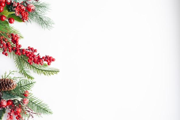 Kerstkaart, vuren twijgen, rode bessen en kegels, bestrooid met sneeuw ,, kopie ruimte