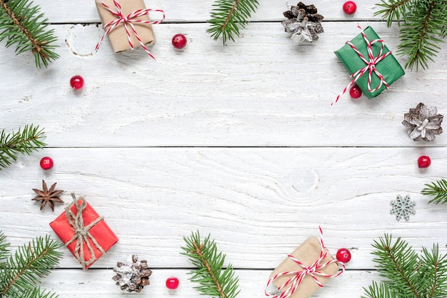 Kerstkader gemaakt van dennentakken, rode bessen, geschenkdozen en dennenappels