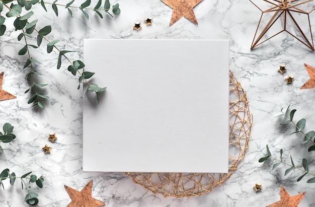 Kerstkader met verse eucalyptustakjes en geometrische versieringen - zeshoeken, metalen draadvormen. trendy bovenaanzicht op witte marmeren achtergrond. kopieer ruimte op wit doek.