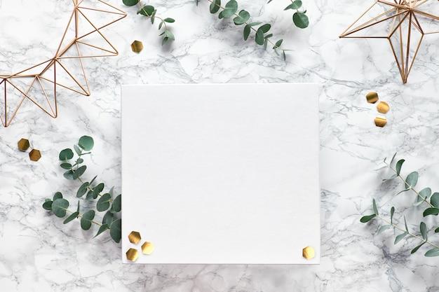 Kerstkader met verse eucalyptustakjes en gouden geometrische versieringen - zeshoeken en geometrische draadvormen. plat lag, bovenaanzicht op witte marmeren achtergrond, plaats voor tekst, kopie-ruimte.