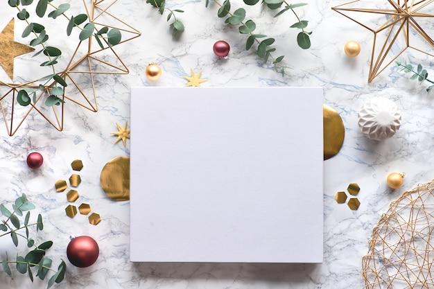 Kerstkader met verse eucalyptustakjes en gouden geometrische versieringen - zeshoeken, snuisterijen en draadvormen. plat lag, bovenaanzicht op witte marmeren achtergrond met kopie-ruimte, plaats voor uw tekst ..