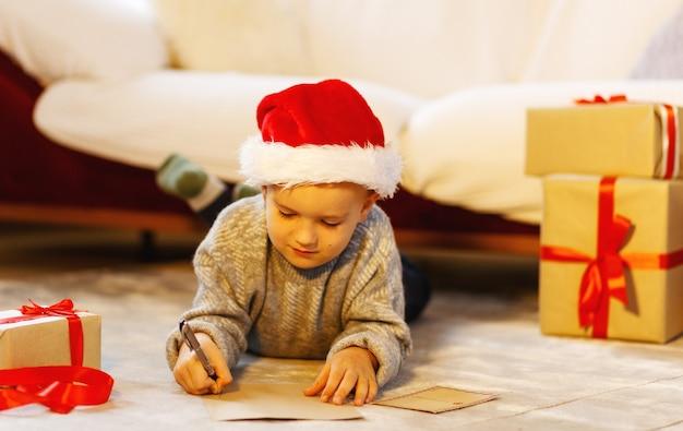 Kerstkind schrijf een brief aan de kerstman in een kerstmuts schrijf een verlanglijstje naast de kerstboom