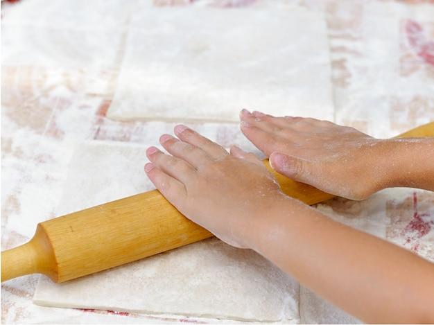 Kerstkoekjes bakken, kind handen snijdt deeg