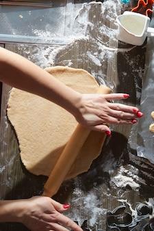 Kerstkoekjes bakken op donkere bruine houten tafel. familie die peperkoekman maken, koekjes van peperkoekdeeg, van bovenaf bekijken.