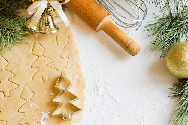 Kerstkoekjes, deegroller en cookie cutters op witte tafel achtergrond. kopieer ruimte
