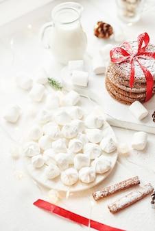 Kerstkoekjes en marshmallows op een wit bij het raam