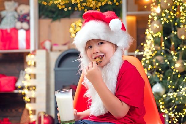 Kerstkoekjes en melk. kleine jongen van de kerstman met baard en snor. kerstman in huis. de kerstman