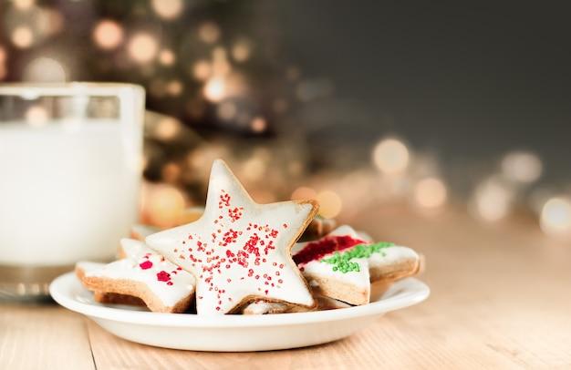 Kerstkoekjes en melk voor de kerstman op de achtergrond van een defocuskerstboom