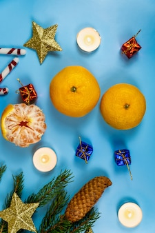 Kerstkoekjes geschenken kaarsen en mandarijnen op een blauw.