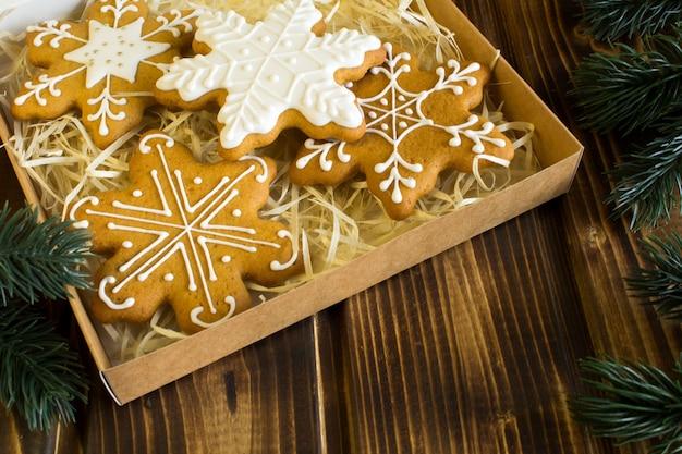 Kerstkoekjes in de doos op de bruine houten achtergrond
