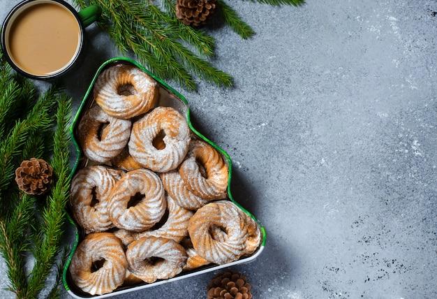 Kerstkoekjes in een doos in de vorm van een kerstboom. groene takken met denneappels.