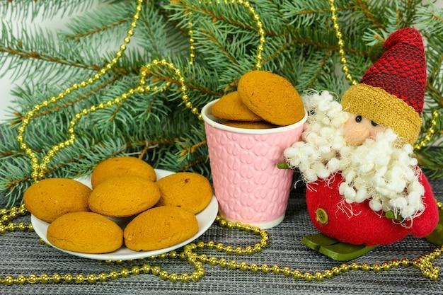 Kerstkoekjes in een glas en een bord, santa claus op de achtergrond van dennentakken.
