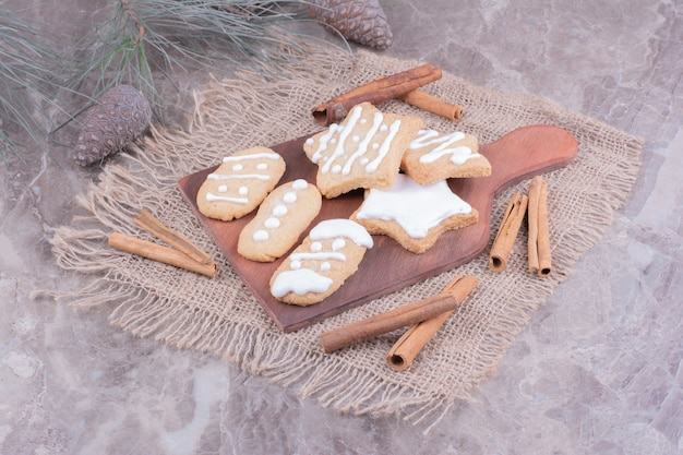 Kerstkoekjes in ovale en stervormen op een houten bord met kaneelstokjes rond