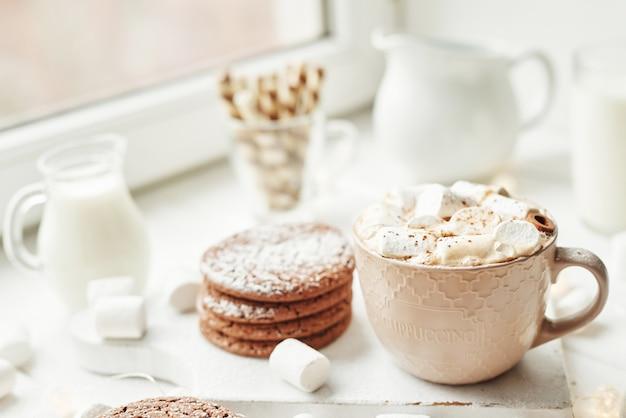 Kerstkoekjes, melk, cacao, marshmallows, meringue bord bij het raam