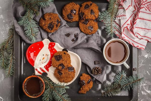Kerstkoekjes met chocolade en kopje cacao, donkere achtergrond. kerst achtergrond concept.