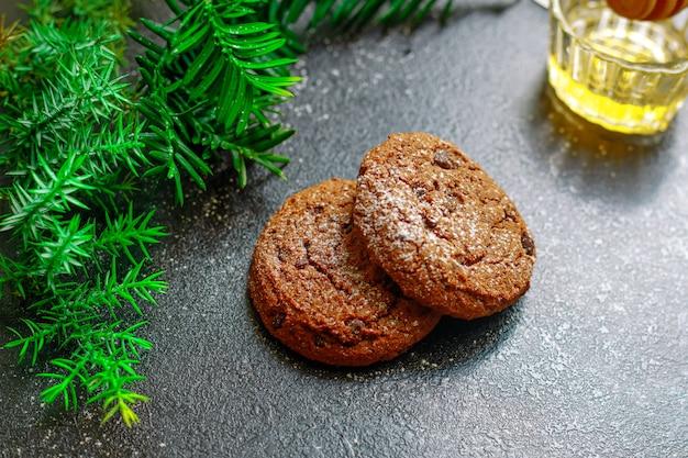 Kerstkoekjes met chocolade in poedersuiker naaldhout tak op tafel